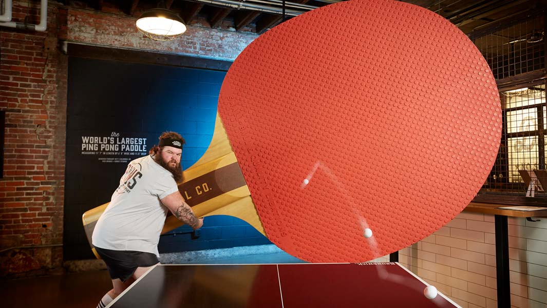 The largest table tennis / ping pong bat is 3.53 m / 11 ft 7.8 in tall and 2.02 m 6 ft 7.8 in wide
